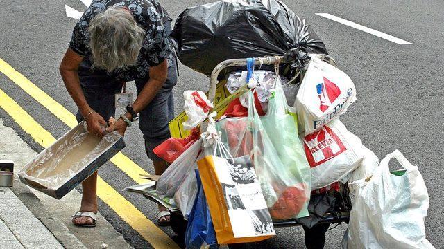 Singapur sokaklarında bir kadın, eski eşyaları toplayıp el arabasına atıyor.