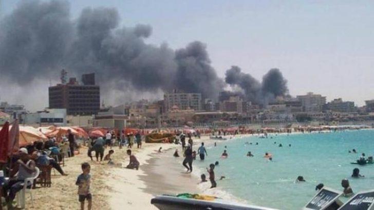 Bombaların gölgesinde denize giriyorlar