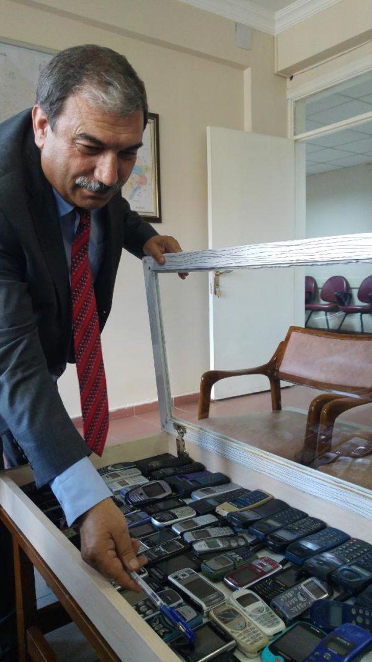 Belediye Başkan Yardımcısı, eski cep telefonlarını sergiliyor