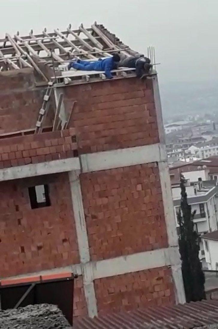 İşçilerinin çatı kenarından sarkarak çalışması görenleri şaşırttı