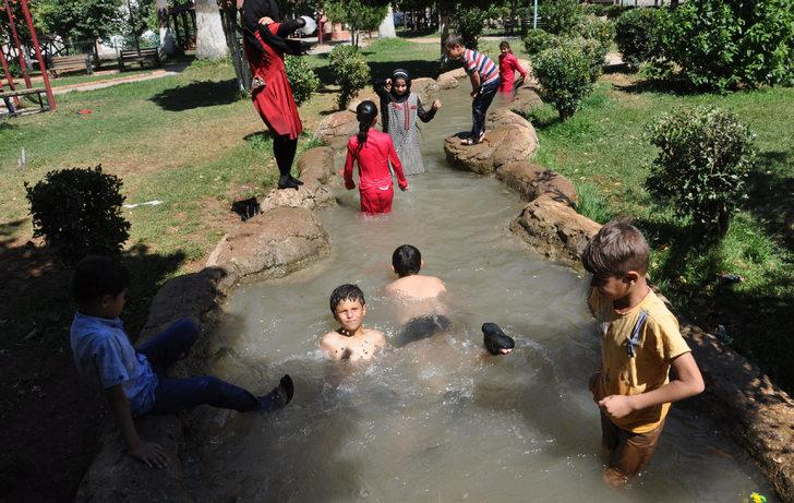 Sıcaktan bunalan çocuklar, süs havuzunda serinliyor
