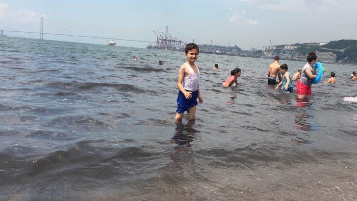 Kömür karası akan derenin yanında denize giriyorlar